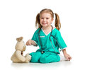 Girl with clothes of doctor playing with toy over white Stock Photos