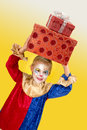 Girl clown with presents smiling big on her head Stock Photography