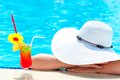 Girl with a cocktail in the pool covered her head hat from sun Royalty Free Stock Image