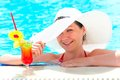 Girl with a cocktail at the pool holding a hat hand happy Stock Photos