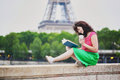 Girl with coffee to go reading a book near the Eiffel tower. Royalty Free Stock Photo