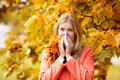 Girl with cold rhinitis on autumn background fall flu season i ill sick sneezing woman handkerchief vaccine against influenza Royalty Free Stock Images