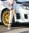 stock image of  Girl in colored sneakers shoes and in white trousers on background of white car. Girl on car background