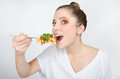 Girl in colorful makeup is eating spaghetti with a fork hungry and tied her hair Stock Photography