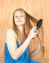 Girl combing her long hair Stock Images