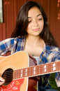 Girl concentrating on playing guitar Stock Photography