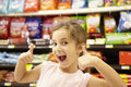Girl in confectionery supermarket confectionery aisle Royalty Free Stock Image