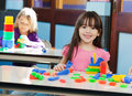 Girl with construction block while friend playing portrait of cute little in background at preschool Royalty Free Stock Images