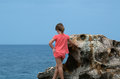 Girl contemplating the sea little by rocky coast looking out to view from behind Stock Images