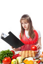Girl the cook prepares according to the book Stock Images