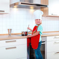 Girl cooking in modern kitchen Stock Images