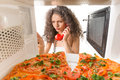 Girl cooking a pizza preparing and talking on the phone Royalty Free Stock Photo