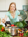 Girl cooking with vegetables in domestic kitchen ladle from Stock Image