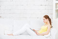 Girl on the couch with a digital tablet. Housewarming. Royalty Free Stock Photo