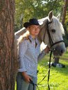 Girl-cowboy and white horse Stock Images