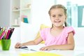 Girl with crayons cute little sitting by table and open copybook in front of her Stock Image