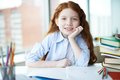 Girl with crayons cute little sitting by table and open copybook in front of her Stock Photo