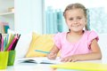 Girl with crayons cute little sitting by table and open copybook in front of her Royalty Free Stock Photography