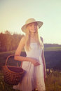Girl with crib in summer field retro toned portrait of blonde teenage straw hat basket posing Stock Photos