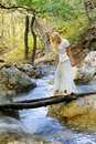 Girl crossing forest river by wooden bridge Royalty Free Stock Image