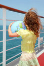 Girl on cruise liner deck and holding globe