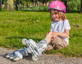 Girl crying with helmet on but without protective knee pads Stock Photos