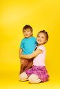 Girl cuddle standing child while sitting on floor her haunches the the yellow background Royalty Free Stock Image