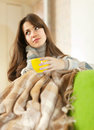 Girl with cup of tea sitting on sofa in livingroom Royalty Free Stock Photography