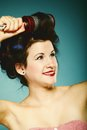 Girl in curlers with hairbrush styling hair Royalty Free Stock Photo