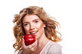 Girl with curly hair holding a red apple and smiling. Royalty Free Stock Photo
