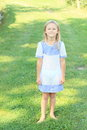 Girl in cute dress barefoot white and blue standing on green grass Royalty Free Stock Photos
