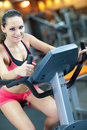 Girl  is cycling in fitness hall Stock Photography