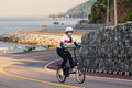 The girl cycling uphill on the road Royalty Free Stock Photo