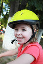 Girl cyclist in a bicycle helmet on the park cute simle wearing green smiling Royalty Free Stock Images