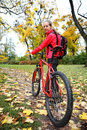 Girl cyclist with bike on bicycle walk in autumn park young and backpack Stock Image