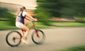 Girl cyclist in traffic on the city roadway intentional motion blur and color shift Stock Photos