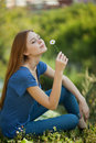 Girl with daisies sits on the grass and sniff it Royalty Free Stock Image