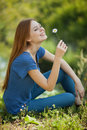 Girl with daisies sits on the grass and sniff it Stock Photography