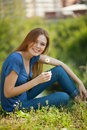 Girl with daisies sits on the grass and sniff it Royalty Free Stock Photos