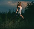 Girl dancing in grass summer at sunset toned image Royalty Free Stock Images