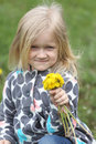 Girl with dandelions young blonde bunch of on a green lawn Royalty Free Stock Photography