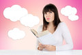 Girl daydreaming while reading a book and looking up on a pink Royalty Free Stock Photo