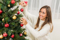 Girl decorating christmas tree happy beautiful young woman with red ornament at home Stock Photos