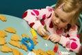 Girl decorating xmas cookies cute preschool sat at table Royalty Free Stock Photos