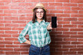 Girl demonstrate on smartphone beautiful young dark haired in casual clothes hat and eyeglasses posing smiling and standing Royalty Free Stock Images