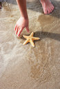 Girl Discovering Starfish On Beach Royalty Free Stock Photo