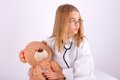 Girl doctor treated her teddy bear dressed as a his Stock Photography