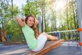 Girl does crunches on the board at sports ground wooden during summer sunny day outside Stock Photography