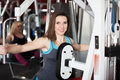 Girl does exercises for arms and shoulders in gym smiling sportswear on training apparatus fitness center Stock Photos