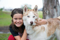 Girl and dog cute smiling hugging her beautiful red white siberian husky in a park Stock Photos